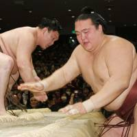 Tough and focused: Hakuho (left) emerges victorious in a match against Kisenosato on Wednesday in the New Year Grand Sumo Tournament. | KYODO
