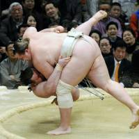 One down: Baruto throws Gagamaru on the first day of the Spring Grand Sumo Tournament in Osaka on Sunday. | KYODO