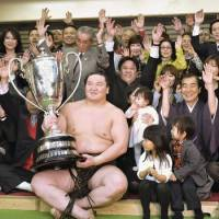 Day of drama: Hakuho, surrounded by his supporters, earns his 22nd Emperor's Cup on Sunday after winning twice on the final day of the Spring Grand Sumo Tournament. | KYODO