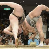 Going down: Hakuho (left) and Toyonoshima lean over the ring during their bout at the Summer Grand Sumo Tournament on Monday. Toyonoshima emerged the victor. | KYODO