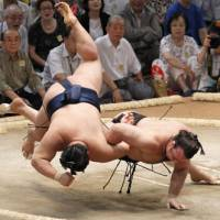 Down under: Kotooshu (right) touches the ground to lose his match against Goeido at the Nagoya Grand Sumo Tournament on Monday. | KYODO