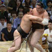 Moment of truth: Harumafuji (left) pushes Hakuho out of the ring at the Nagoya Grand Sumo Tournament on Sunday. | KYODO