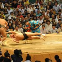 Ozeki Harumafuji goes flying as he pushes Toyonoshima from the ring on Day 8 of the Nagoya Basho. MARK BUCKTON PHOTO | MARK BUCKTON PHOTO
