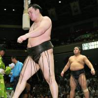 Disappointed: Yokozuna Hakuho (front) walks out of the ring after a loss to Tochiozan on Tuesday at the Autumn Grand Sumo Tournament in Tokyo. | KYODO