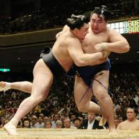 Business as usual: Harumafuji (right) improves to 14-0 in the Autumn Grand Sumo Tournament by beating fellow ozeki Kakuryu on Saturday. | KYODO