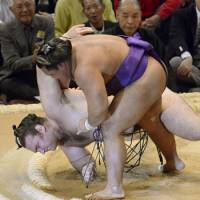 Hometown favorite Shohozan downs ozeki Bulgarian Kotooshu with a sukuinage on the first day of the Kyushu Grand Sumo Tournament. | KYODO