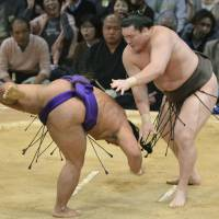Powerful technique: Yokozuna Hakuho defeats No. 2 maegashira Shohozan on Friday at the Kyushu Grand Sumo Tournament. | KYODO