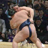 To the limit: Harumafuji (rear) is pushed onto the straw bales by Goeido during their bout at the Kyushu Grand Sumo Tournament on Monday. | KYODO