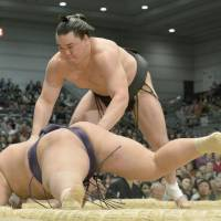 Total control: Harumafuji pushes Tochiozan to the ground on the opening day of the Spring Grand Sumo Tournament in Osaka on Sunday. | KYODO