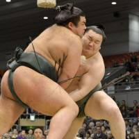 Many happy returns: Hakuho (rear) tussles with Takayasu at the Spring Grand Sumo Tournament in Osaka on Monday. | KYODO