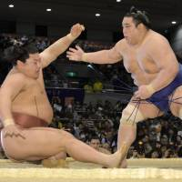 In control: Wakanosato (right) claims victory over Yoshikaze on Monday at the Spring Grand Sumo Tournament in Osaka. | KYODO