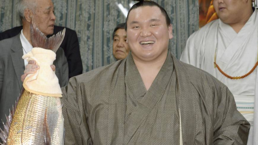 Fresh on the menu: Hakuho holds his celebration fish after winning his 24th career title at the Spring Grand Sumo Tournament in Osaka on Friday.