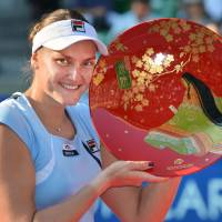 Breakthrough: Russia's Nadia Petrova holds up her prize after beating Poland's Agnieszka Radwanska 6-0, 1-6, 6-3 in the final of the Pan Pacific Open on Saturday at Ariake Colosseum. | AFP-JIJI