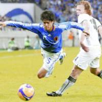 Hard-fought battle: Japan defender Atsuo Uchida is fouled by Uzbekistan's Vitaly Denisov during Wednesday's final Asian qualifier game for the 2010 World Cup at Saitama Stadium 2002 on Wednesday night. The game ended in a 1-1 tie.   KYODO PHOTO