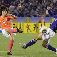 On target: South Korea midfielder Kim Jae Sung scores a 70th-minute goal against Japan goalkeeper Seigo Narazaki on Sunday in the East Asian Football Championship at National Stadium. South Korea won 3-1. | KYODO PHOTO
