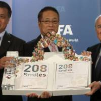 Pop art: JFA secretary general Kohzo Tashima (left), JFA president Motoaki Inukai (center) and FIFA president Sepp Blatter hold Japan's 2022 World Cup Bid Book in Zurich on Friday. | KYODO PHOTO