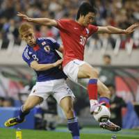 Active feet: Japan midfielder Keisuke Honda (left) and South Korea defender Kwak Tae Hwi compete for the ball in the first half of Monday's international friendly at Saitama Stadium 2002. South Korea won 2-0. | KYODO PHOTO