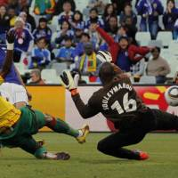 Super strike: Keisuke Honda scores past Cameroon's Stephane Mbia (left) and goalkeeper Hamidou Souleymanou in Group E action at the World Cup on Monday in Bloemfontein, South Africa. Japan won 1-0. | AP PHOTO