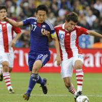 Japan's Makoto Hasebe (left) vies for the ball with Paraguay's Edgar Benitez during Tuesday's match in Pretoria. Paraguay advanced to the quarterfinals by beating Japan 5-3 on penalties. | KYODO PHOTO