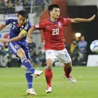 Fierce rivalry: Japan captain Makoto Hasebe (left) fires a shot against South Korea in Tuesday's friendly match in Seoul. The game ended in a scoreless draw. | KYODO PHOTO