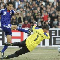 Successful start: Japan's Yasuyuki Konno scores a 36th-minute goal past Tajikistan goalkeeper in Friday's 2014 World Cup qualifier in Dushanbe. Japan beat the hosts 4-0. | KYODO