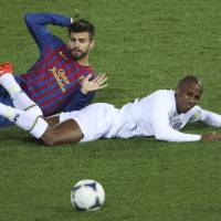 It wasn't me: Barcelona defender Gerard Pique (left) protests his innocence after tangling with Santos striker Borges during the Club World Cup final in Yokohama on Sunday. | AP PHOTO