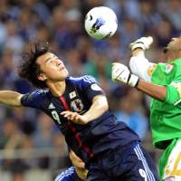 Flying start: Shinji Okazaki challenges Oman goalkeeper Ali Al Habsi during Japan's 3-0 win in their World Cup qualifying match in Saitama on Sunday night. | AFP-JIJI