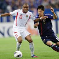 Compete to win: Japan's Shinji Kagawa (right) and Jordan's Khalil Baniateyah vie for the ball during their World Cup qualifying match at Saitama Stadium on Friday. | AP