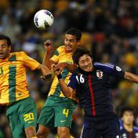 Go get it: Australia's Alex Brosque (center) and Tim Cahill leap over the head of Japan's Yuzo Kurihara in Tuesday's World Cup Group B qualifier in Brisbane, Australia. The match ended in a 1-1 draw. | AFP-JIJI