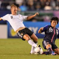 Dominating effort: Germany's Melanie Leupolz (left) competes with Japan's Hikari Takagi for the ball in their Under-20 Women's World Cup semifinal match at National Stadium on Tuesday. Leupolz scored a first-minute goal in Germany's 3-0 triumph. | AFP-JIJI