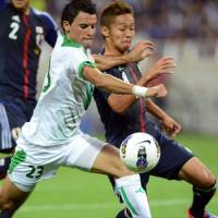 One step closer: Japan's Hiroshi Kiyotake (right) tussles with Iraq's Walid Salem during their World Cup qualifier in Saitama on Tuesday night. Japan won 1-0. | AFP-JIJI