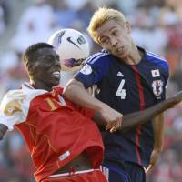 Ahead of his time: Keisuke Honda, right, vies for the ball during Japan's 2-1 victory over Oman on Tuesday. | KYODO