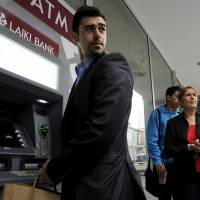 Exit strategy: Cypriots wait to use the ATM of a closed branch of the Cyprus Popular Bank in Limassol on  Thursday. | AP