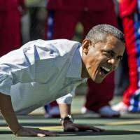 Strengthening his legacy: U.S. President Barack Obama does pushups during the annual Easter Egg Roll on the White House's South Lawn last April in Washington. | AFP-JIJI