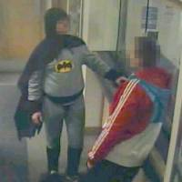 Kapow!: A man dressed as Batman hands over a suspect to police in the  West Yorkshire city of Bradford early  Thursday. | KYODO