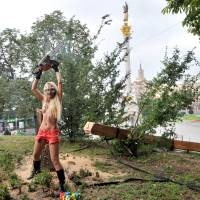 Chain saw Mass: Femen's Inna Shevchenko raises a chain saw after cutting down a cross erected in Kiev in memory of victims of political repression.  The cross was felled in a gesture of support for Russian punk band Pussy Riot after its members were charged with hooliganism. | AFP-JIJI