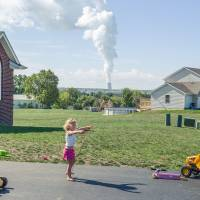 A girl jumps rope as steam rises from the Byron nuclear plant's cooling towers on the town's outskirts late last year. The plant produces electricity that serves more than 2 million homes.  |  Andrew BorowIec