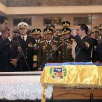 Transition of power: Venezuela's Acting President Nicolas Maduro (left) holds a miniature copy of Venezuela's constitution during a symbolic swearing-in ceremony in front of the late President Hugo Chavez's coffin on March 8 in Caracas. | AP