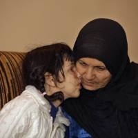 Civilian tragedy: Shams Karim, 7, who was blinded and scarred by the bomb that killed her mother six years ago, cuddles up to her grandmother in Baghdad. She takes tranquilizers to control outbursts of crying and screaming. | AP