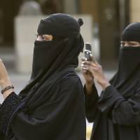 A snapshot of Saudi life: Women take pictures outside a Riyadh mosque as residents perform morning prayers to mark the end of the holy fasting month of Ramadan. | AP