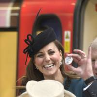 Badge of honor: Kate, the Duchess of Cambridge, receives a 'Baby on Board' badge during a visit to London's Baker Street station with Queen Elizabeth II on Wednesday. | AP