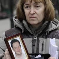 Silenced: Nataliya Magnitskaya holds a portrait of her son Sergei Magnitsky, who died in jail in 2009. He was arrested on tax evasion charges after he alleged Russian officials and organized criminals conspired to claim $230 million in tax rebates. | AP
