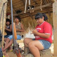 Digital tribe:  Teenage girls make jewelry to sell to visitors in Lapetanha, one of the forested Brazilian hamlets where the Paiter Surui people live, in December. | THE WASHINGTON POST
