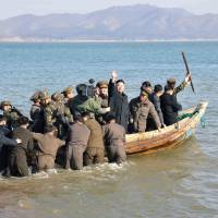 Rallying the troops: North Korean leader Kim Jong Un waves at military officers after inspecting the Wolnae Islet Defense Detachment, near the country's western sea border with South Korea, on March 11. | AP