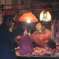 Easy pickings: A street vendor sells pork from a market stall in Shanghai in February. | BLOOMBERG