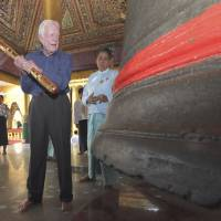 Going to bat for democracy: Former U.S. President Jimmy Carter gets ready to hit a giant bell during his visit to Yangon's famed Shwedagon Pagoda on Friday. Carter arrived Tuesday to support Myanmar's ongoing democratic transition. | AP