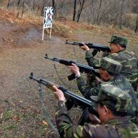 No love lost: North Korean soldiers take aim at a target featuring an image of South Korean Defense Minister Kim Kwan Jin at an undisclosed location on Saturday. | AFP-JIJI