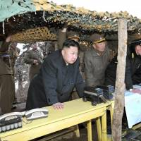 Drilling it in: North Korean leader Kim Jong Un (left) inspects landing drills by the Korean People's Army on March 25. | AFP-JIJI
