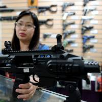 Firepower to spare: A sales assistant demonstrates how to convert a 9 mm handgun into a compact submachinegun at a weapons store in Manila on April 4. | AFP-JIJI