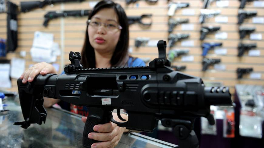 Firepower to spare: A sales assistant demonstrates how to convert a 9 mm handgun into a compact submachinegun at a weapons store in Manila on April 4.